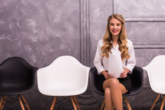 Young businesswoman holding laptop while sitting on chair Royalty Free Stock Photo