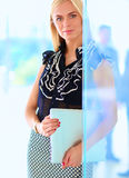 Young businesswoman holding a laptop, standing on office Stock Photos