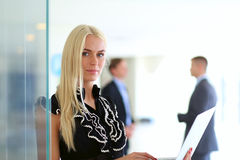 Young businesswoman holding a laptop, standing on office Stock Image