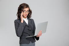 Young businesswoman holding laptop and touching her glasses. Young pretty concentrated confident businesswoman holding laptop and touching her glasses royalty free stock image