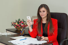 Young businesswoman holding mobilephone in hand, writing text message, sitting at desk. Stock Images