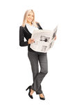 Young businesswoman holding a newspaper and leaning against a wa Royalty Free Stock Photo