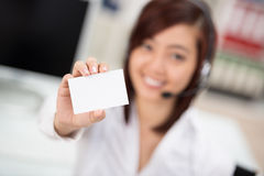 Young businesswoman holding out a blank card Stock Photo