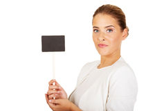 Young businesswoman holding small empty advertising board Royalty Free Stock Images