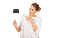 Young businesswoman holding small empty advertising board Royalty Free Stock Photos