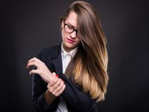 Young businesswoman holding sore wrist in her hand. Young businesswoman in formal suit holding sore wrist in her hand royalty free stock photo