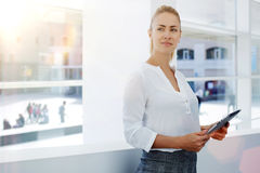 Young businesswoman holding touch pad and thinking about forthcoming meeting with important partners, Royalty Free Stock Photography