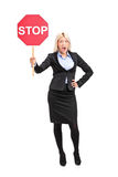 Young businesswoman holding a traffic sign stop. Full length portrait of a young businesswoman holding a traffic sign stop  on white background Royalty Free Stock Images