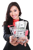 Young businesswoman holding trolley and money Royalty Free Stock Photo