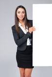 Young businesswoman holding white blank poster. Royalty Free Stock Photo