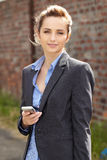 Young businesswoman holds her mobile, outdoor Stock Images