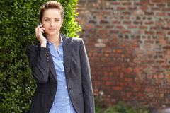 Young businesswoman holds her mobile, outdoor Royalty Free Stock Images