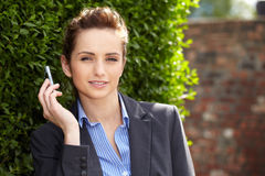 Young businesswoman holds her mobile, outdoor Stock Photography