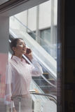 Young businesswoman inside the building talking on the phone Royalty Free Stock Image