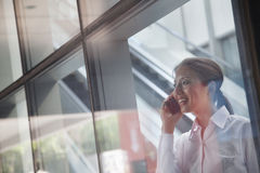 Young businesswoman inside the building talking on the phone and looking through the glass Stock Photo