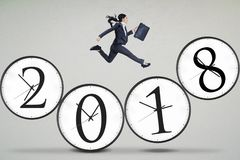 Young businesswoman jumping above clocks Stock Photo