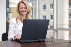 Young businesswoman with laptop. Successful young businesswoman with laptop computer in the office Stock Photography