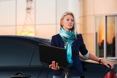 Young businesswoman with laptop. On the car parking Royalty Free Stock Photo