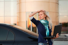 Young fashion business woman with laptop by her car Royalty Free Stock Photography