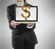 Young businesswoman with laptop and dollar money sign in hand Stock Images