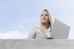 Young businesswoman with laptop looking away on terrace against sky Stock Images