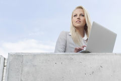 Young businesswoman with laptop looking away on terrace against sky Stock Photography