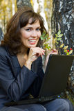 Young businesswoman with laptop on nature. Royalty Free Stock Photo