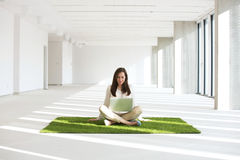 Young businesswoman with laptop while sitting on grass carpet in empty office Stock Images