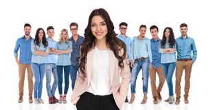 Young businesswoman leader relaxing with her casual team. With hands in pockets after a productive day of work. They are standing on a white background wearing royalty free stock images