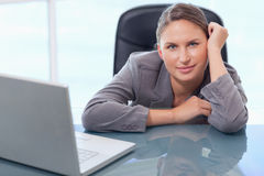 Young businesswoman leaning on her desk Royalty Free Stock Images