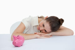 Young businesswoman leaning on her desk with a piggy bank Royalty Free Stock Photos