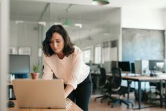 Free Young Businesswoman Leaning Over Her Office Desk Using A Laptop Royalty Free Stock Photography - 160625687