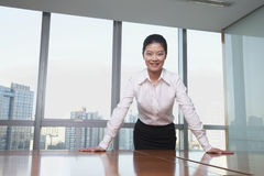 Young businesswoman leaning on table in office, portrait Stock Image
