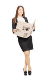 Young businesswoman leaning on a wall and holding a newspaper Stock Images
