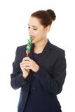 Young businesswoman licking a lolipop Stock Photo