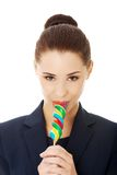 Young businesswoman licking a lolipop Stock Images