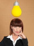 Young businesswoman with light bulb, thinking Royalty Free Stock Photo