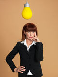 Young businesswoman with light bulb, thinking Royalty Free Stock Photography