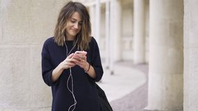 Young businesswoman listening to music and dancing outside. Young woman wearing a black business suit is listening to the music with her smartphone and stock video