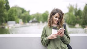 Young businesswoman listening to music and drinking coffee on bridge. Young woman wearing green casual clothes is listening to the music with her smartphone and stock video footage