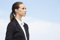 Young businesswoman. Looking away against blue sky stock image