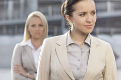 Young businesswoman looking away with female colleague in background Royalty Free Stock Images