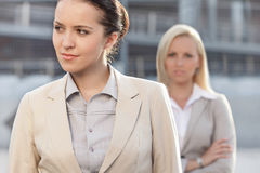 Young businesswoman looking away with female colleague in background Stock Image