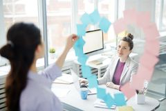 Woman in heart frame. Young businesswoman looking at her colleague behind transparent wall making heart of sticky notepapers Royalty Free Stock Images