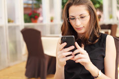 Young businesswoman looking at her smartphone in cafe Royalty Free Stock Photos