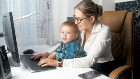 0070278d3 Portrait of young businesswoman looking after her toddler son in office  royalty free stock image