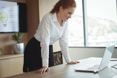 Young businesswoman looking at laptop while leaning on desk Royalty Free Stock Image