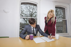 Young businesswoman looking at male colleague signing documents at conference table Royalty Free Stock Photos