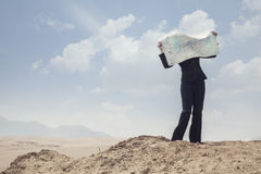 Young Businesswoman looking at a map in the middle of the desert Stock Images