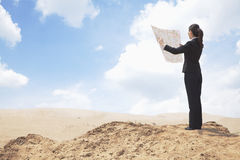 Young Businesswoman looking at a map in the middle of the desert Royalty Free Stock Photo